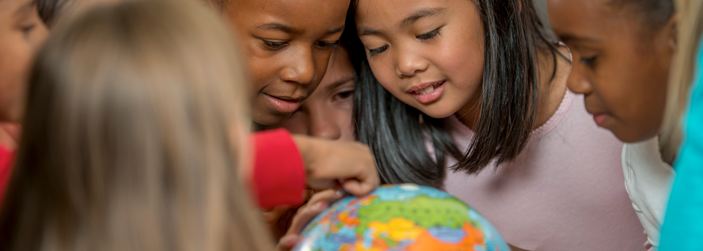 Image of students looking at a globe