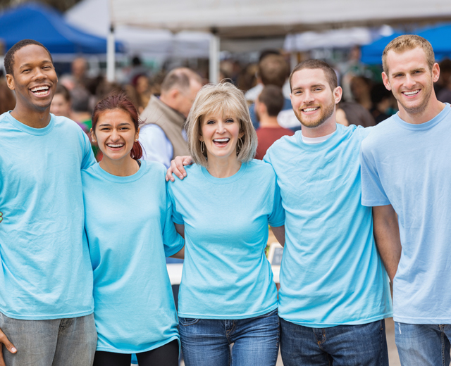 Women and men standing arm in arm in blue tshirts