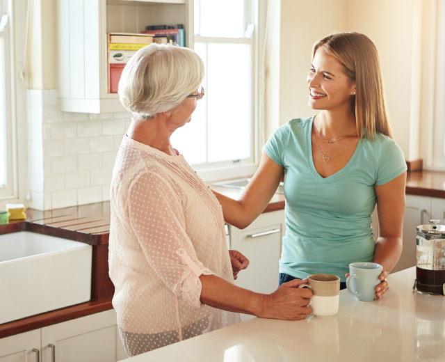 Mother and daughter talking in a kitchen.